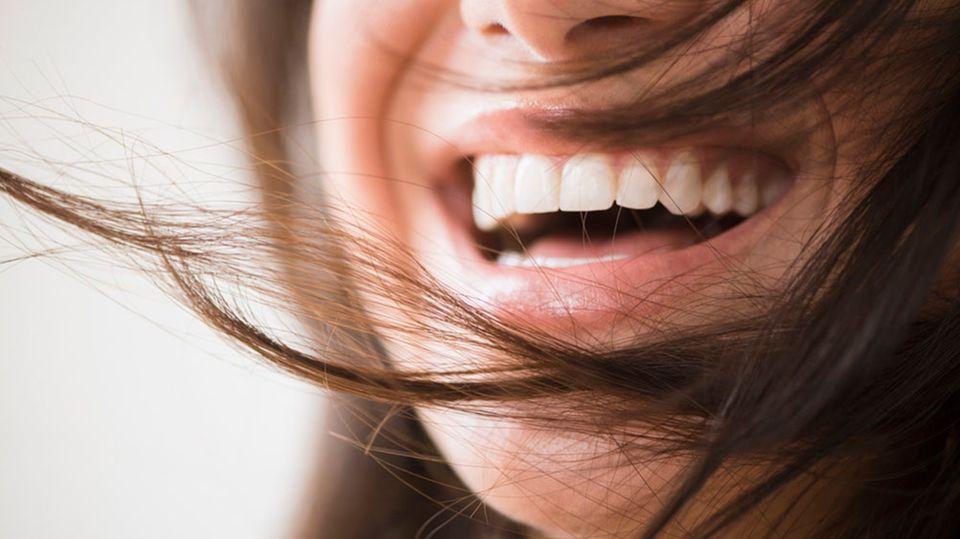 """Bloß keine Hektik  Nach dem Essen muss mandie Zähne putzen - diesen Satz haben viele schon als Kind gehört. Besser ist jedoch, eine gute Stunde zu warten. Dr. Costin Marinescu: """"Durch das Essen bilden sich Säuren im Mund, die den Zahnschmelz angreifbar machen. Wer es eilig hat, spült den Mund mit Wasser aus und nimmt ein Zahnkaugummi. Das regt den Speichelfluss an, wodurch sich der pH-Wert im Mund neutralisiert.""""    Weniger - und Druck rausnehmen  """"Es reicht aus, sich morgens und abends die Zähne zu putzen"""", sagt Dr. Marinescu. """"Wenn man es richtig macht. Oft wird die Zahnbürste zu stark aufgedrückt. Dadurch gehen die Borsten zur Seite und gelangen nicht in die Zahnzwischenräume.""""  Weiß, aber ...  Kennt ihr den Begriff """"Radioactive Dentin Abrasion""""? Der RDA-Wert gibt bei Zahnpasten, wie abrasiv, also abschleifend, sie wirken. Bei Whitening-Cremes ist er besonders hoch. Doch: """"Je höher der Wert, desto mehr Zahnsubstanz wird abgetragen. Produkte mit einem RDA-Wert über 50 nicht dauerhaft benutzen"""", rät Dr. Costin Marinescu. Leider stehen die Angaben selten auf der Packung, ihr findet sie aber meist im Internet."""