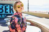Ein leichtes Augenzwinkern ist immer dabei,wenn sich Palmen, Papageien und pralle Farben treffen - die kompromissloseste Art, den Sommer zu verehren.  Oversize-Hemd im Boyfriend-Style und Zigarettenhose in 7/8-Länge: Paul Smith, ca. 270 und 290 Euro.  Verspiegelte Sonnenbrille: Mykita.