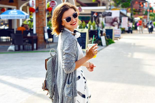 Shopping-Typ: Junge Frau mit Rucksack läuft über eine Straße
