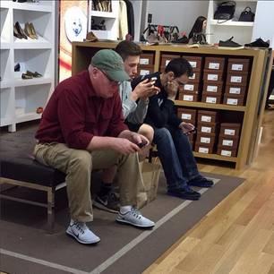 Die Männer warten auf die Frauen beim shoppen