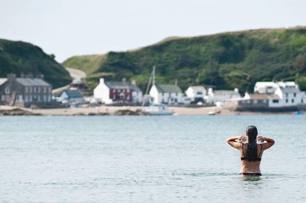 Hartgesottene Wales-Reisende gehen baden: Anna vor der Kulisse des Dörfchens Porthdinllaen auf der Halbinsel Llyn