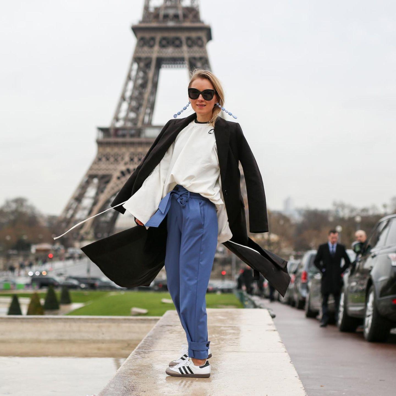 Streetstyle: Eine Frau trägt Sneakers und Stoffhose vor dem Eiffelturm