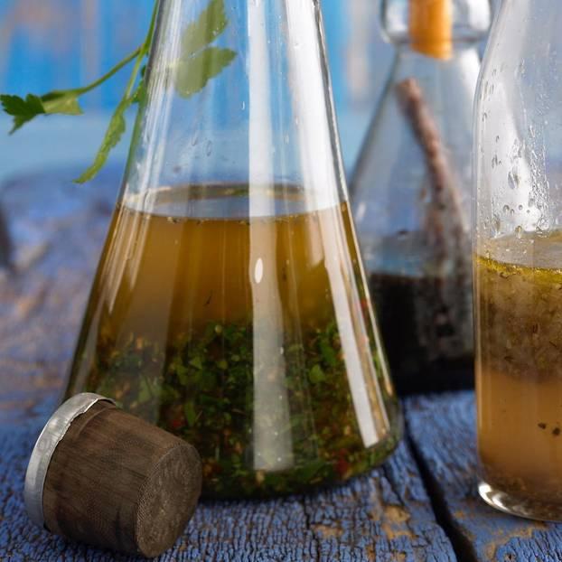 Kräutermarinade wird mit Trichtern in Flaschen abgefüllt