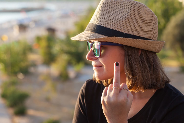 Wie sagt man jemandem, dass man ihn nicht mag: Frau zeigt Mittelfinger