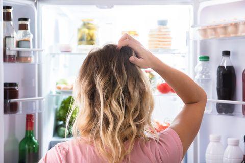 Eine Frau steht vor dem Kühlschrank und kratzt sich am Kopf.