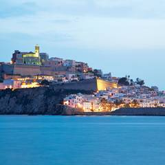 """Fort, Wehrmauer und gestapelte Häuschen: Die """"Dalt Vila"""", die Altstadt Eivissas, liegt wie eine Festung über dem Meer."""