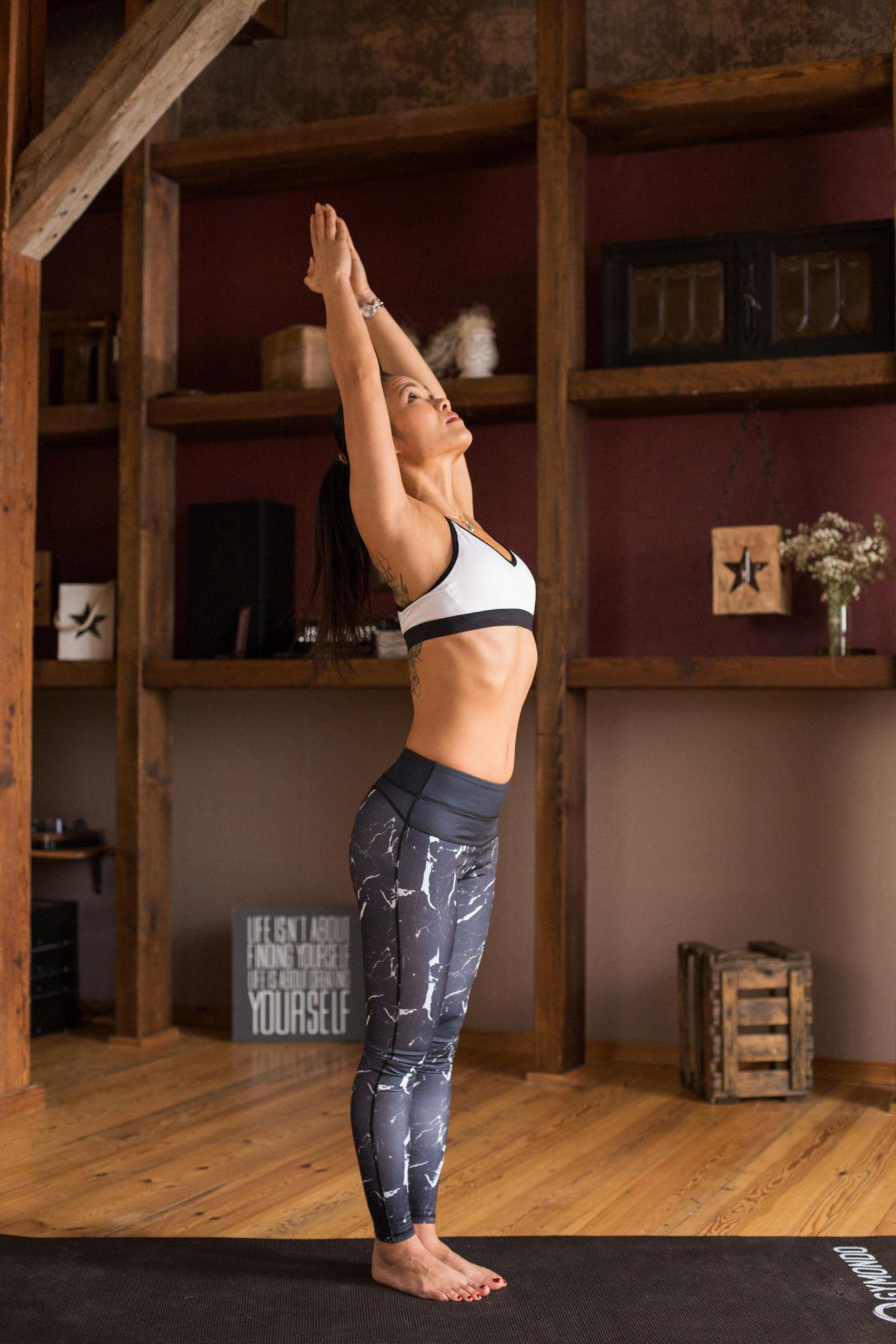 Mit der Einatmung hebst du die Arme und bringst die Handflächen über den Kopf zusammen. Der Blick folgt den Händen. Du kannst die Streckung intensivieren, indem du in eine leichte Rückbeuge gehst. Spanne dabei die Muskulatur von Po und unterem Rücken fest an, um die Lendenwirbelsäule zu schützen. Durch die Streckung dehnst du deine Brustmuskulatur und mobilisierst den Schultergürtel.