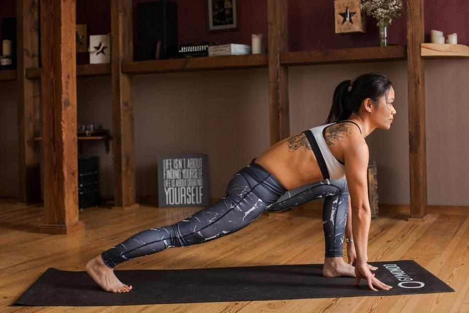 Beim Ausatmen beuge die Knie und komme in die Vorbeuge. Die Handflächen setzt du neben den Füßen ab. Den Oberkörper lässt du auf die Oberschenkel sinken und den Kopf ganz entspannt hängen. Eine leichte Bauchspannung stützt und schützt deine Wirbelsäule in der Vorbeuge. In der Vorbeuge wird die gesamte Körperrückseite gedehnt, Verspannungen werden gelöst.