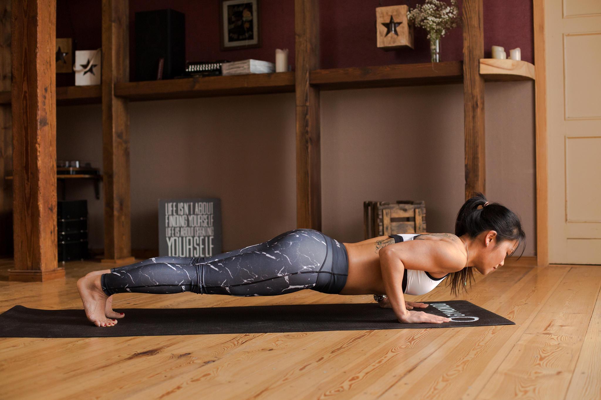Beim Einatmen verlagerst du nun das Gewicht wieder nach vorne, senkst die Hüfte ab und bringst die Schultern über die Hände. Deine Arme bleiben dabei gestreckt. Mit aktiver Spannung der Bauch- und Rückenmuskulatur richtest du den gesamten Körper in einer geraden Linie aus. Fehlt dir noch die Kraft, diese Position sicher und stabil zu halten, kannst du die Intensität verringern, indem du die Knie absetzt.