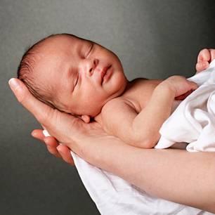 Baby mit Spirale in der Hand