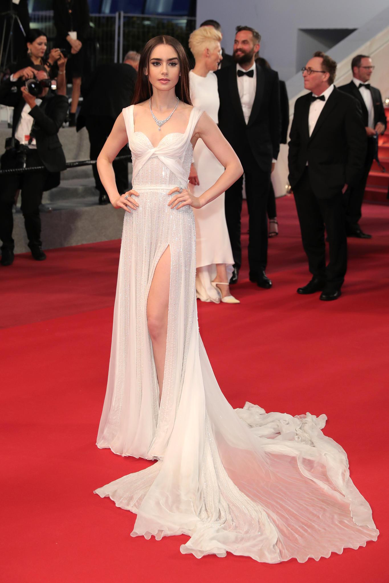 Lily Collins in einem weich fließenden weißen Kleid in Cannes 2017