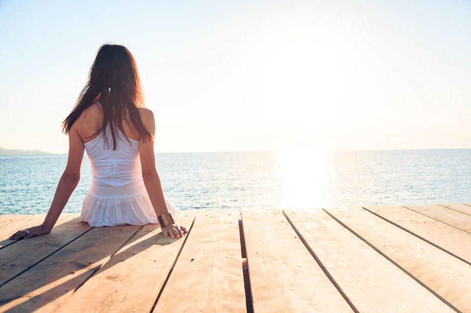 Dauer-Single: Frau sitzt allein am Wasser