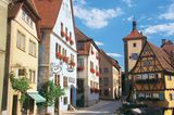 """Rothenburg ob der Tauber, Mittelfranken:Wo huschen Japanerinnen im Dirndl über Kopfsteinpflaster? Wo stehen Ritterrüstungen vor buntem Fachwerk, umklammert eine Stadtmauer verwinkelte Gassen? Natürlich in Rothenburg ob der Tauber. In der berühmtesten deutschen Kleinstadt wetteifert jedes Geschäft, jedes Gasthaus und auch jedes Hotel, wer wohl die längste Geschichte vorweisen kann. So auch die """"Glocke"""". Gegründet im 13. Jahrhundert als Hospital, ist es heute ein gemütliches Hotel mit 23 individuell eingerichteten Zimmern. Ein Weingut gehört auch dazu, und wenn man seinen Lieblingstropfen gefunden hat, ob Scheurebe oder Schwarzriesling, kann man ihn im Laden nebenan kaufen.      Glocke: DZ/F ab 98 Euro (Plönlein 1, Tel. 098 61/95 89 90, www.glocke-rothenburg.de)."""