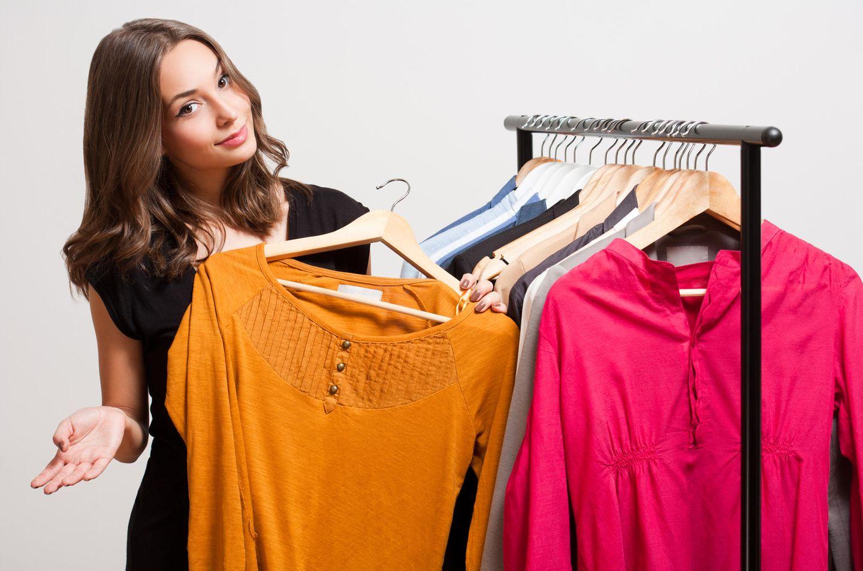 Frau mit orangefarbenem Shirt in der Hand