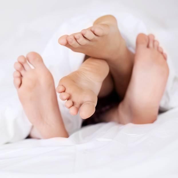 Pille absetzen: Zwei Paar Füße unter einer Bettdecke