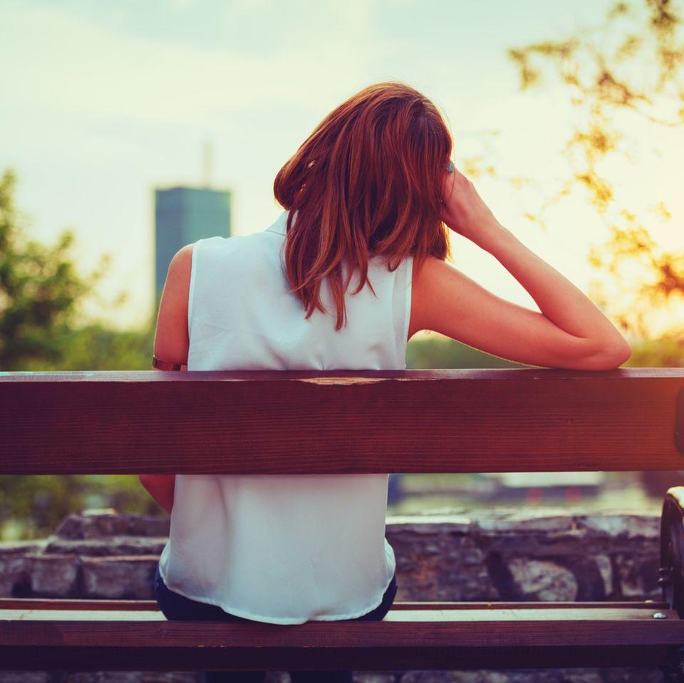 Angewohnheiten, die unglücklich machen: Frau auf Bank