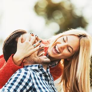 Frau hält Mann die Augen zu und beide lachen