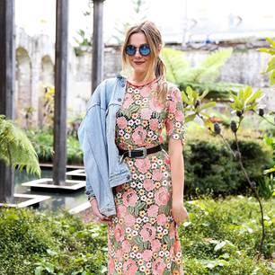 Bloggerin trägt Blumenkleid und Sonnenbrille