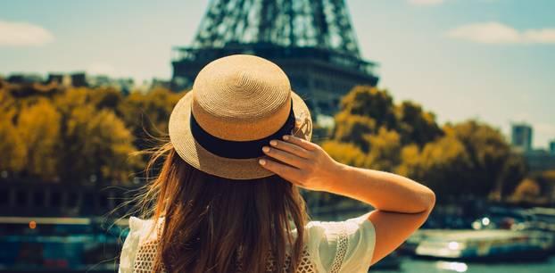 Frau steht vorm Eiffelturm
