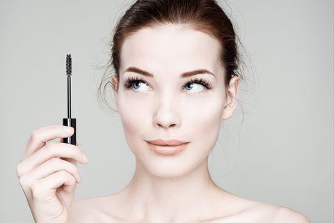 Frau trägt Mascara-Bürste in der Hand