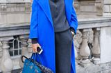 Bloggerin trägt royalblauen Mantel zu roten Schuhen