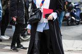 Lena Lademann trägt schwarzen langen Mantel und Hoodie