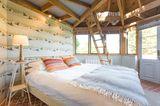 Das Schlafzimmer in Pastell hat großen Charme und die Schlafkoje im Dachgeschoss bietet - falls gewünscht - Platz für einen dritten Gast.