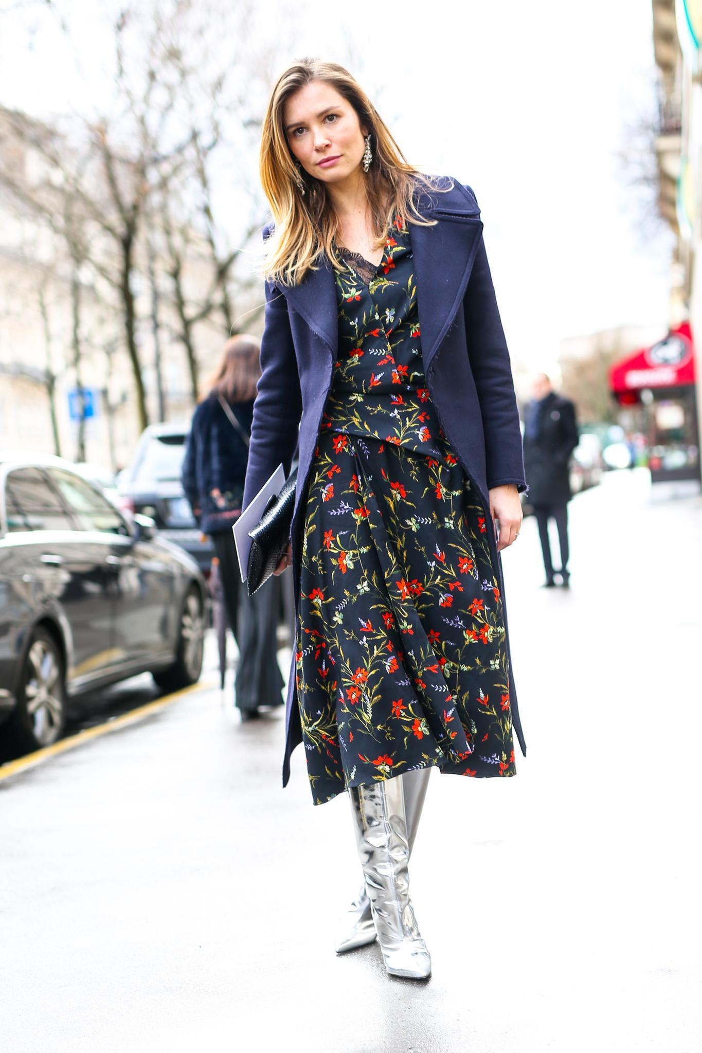 Bloggerin trägt silberne Stiefel zu Blumenkleid und langem Mantel