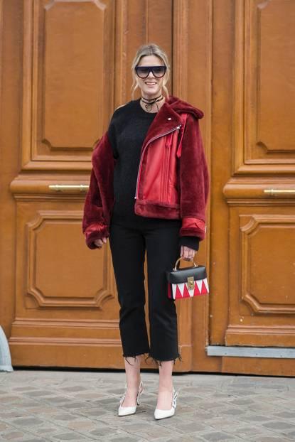 Bloggerin trägt schwarzes Outfit zu roter Lammfelljacke