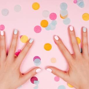 Verschieden lackierte Nägel und Konfetti