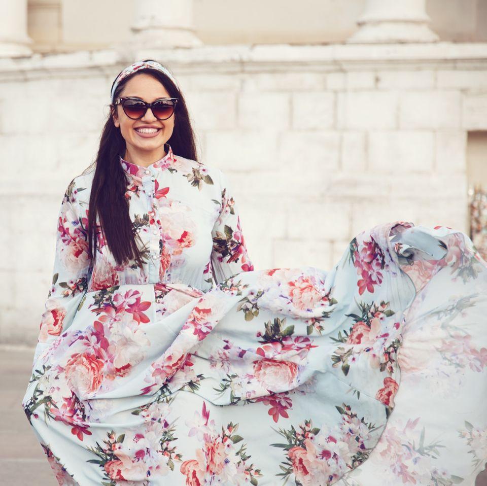 Frau trägt Blumenkleid und Sonnenbrille