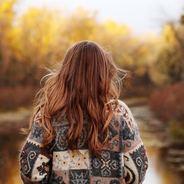 Frau schaut auf herbstliche Bäume
