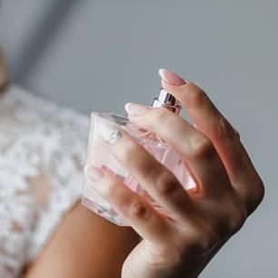 Frau mit Parfum in der Hand