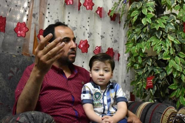 Omran Daknisch: Junge sitzt auf Schoß des Vaters