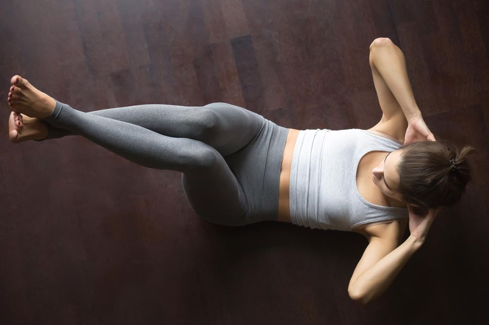Bauch-weg-Übungen: Frau macht Sit-Ups auf dem Boden