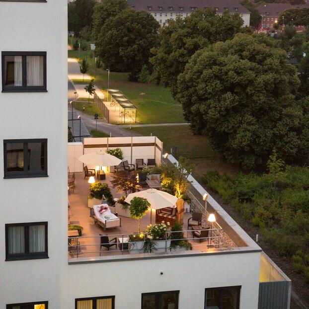 Eine Patientin liegt in ihrem Sterbebett auf der Dachterrasse der Palliativstation unter freiem Himmel.