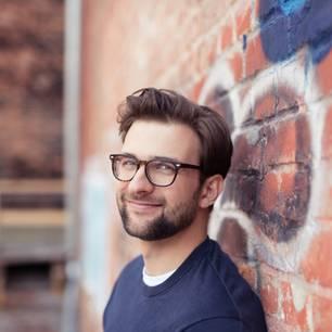 Intelligente Männer: Mann mit Brille vor Steinwand
