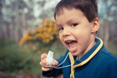 Tröte verschluckt: Ein Junge mit einer Trillerpfeife in der Hand.