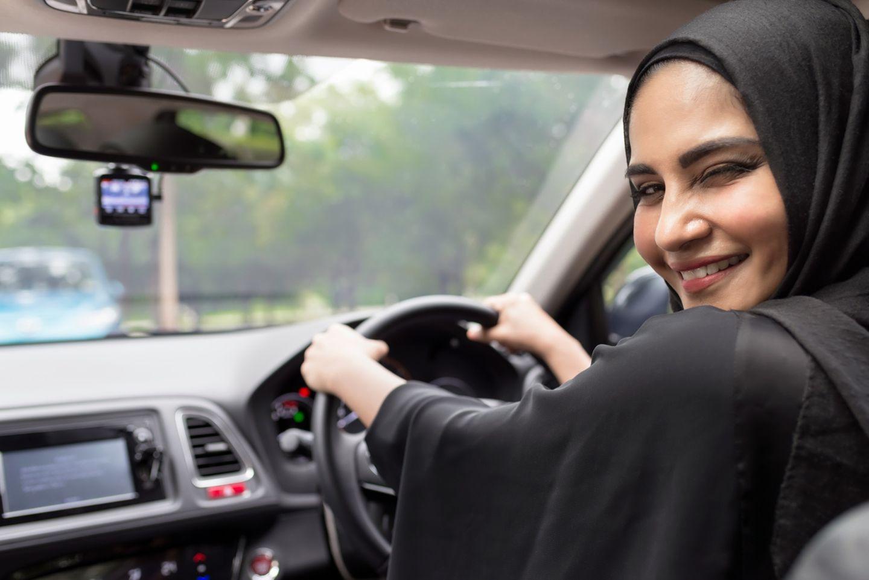 Eine Frau mit schwarzem Kopftuch am Steuer eines Autos.