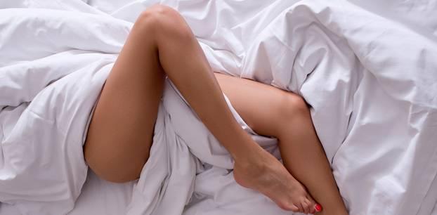 Frau liegt mit nackten Beinen im Bett