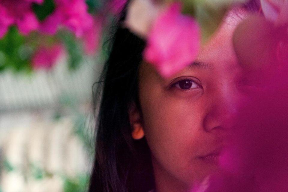 Ein Mädchen, das hinter Blumen posiert