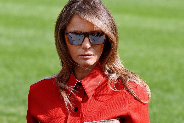 Melania Trump mit Sonnenbrille und hochgeschlossenem roten Outfit.