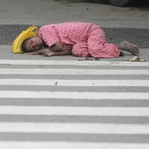 Ein Kind schläft auf einer Straße.