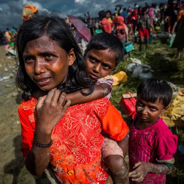Ein Mädchen trägt ein kleines Kind auf dem Rücken, ein anderes steht daneben.