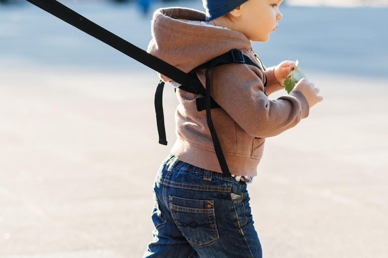 Ein kleiner Junge ist an eine Laufleine gebunden (Symbolbild).