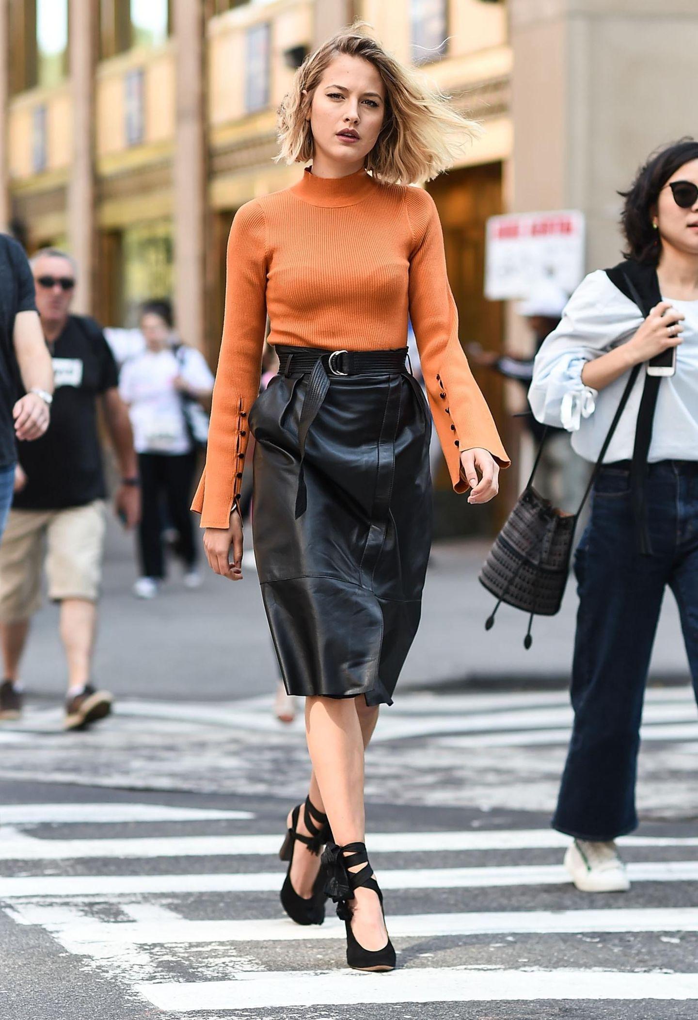 Streetstyle mit schwarzem Lederrock und orangenem Pulli