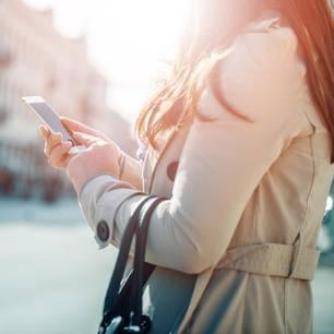 Lügen über WhatsApp: Frau mit Handy
