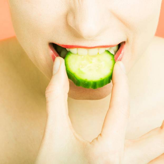 Cucumber Cleanse: Frau mit Gurke