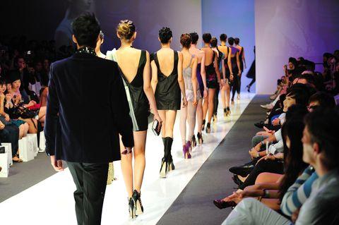 Models laufen auf einem Laufsteg vor Publikum.