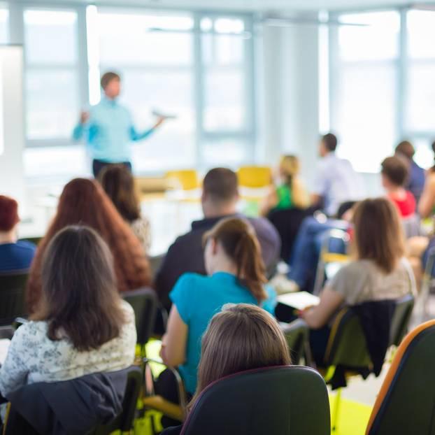 Ein Lehrer spricht vor einer Gruppe Schülern.